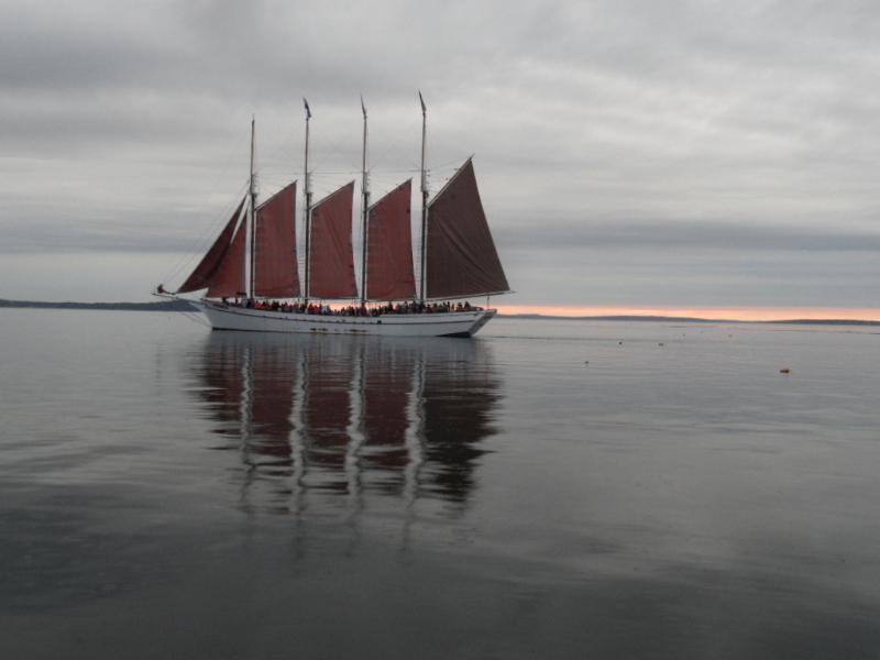 Red sails como el sol se pone detrás de las montañas del Acadia se ve a menudo desde la cercana playa
