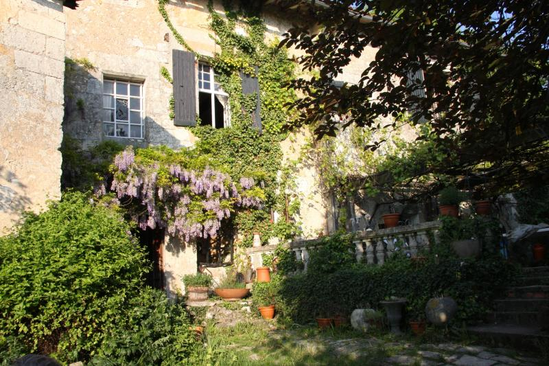 La Bourg~ entrance to living room, master bedroom above the wisteria