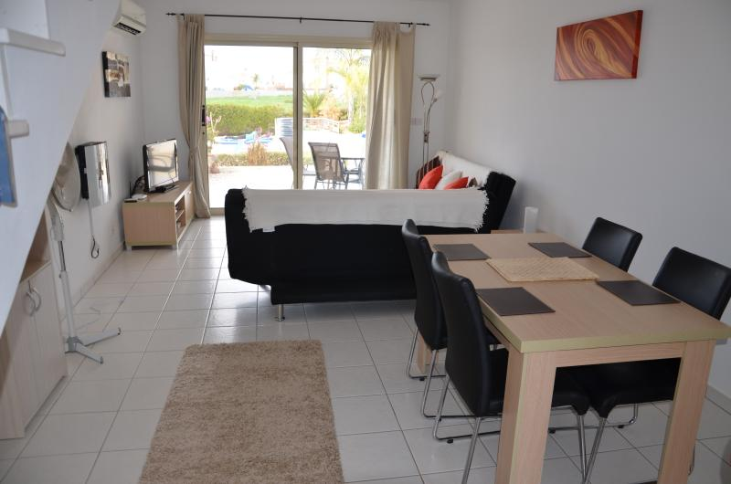 Living area with flatscreen TV, DVD Player, Wii, Playstation 2, 2 x sofa beds and air conditioning.