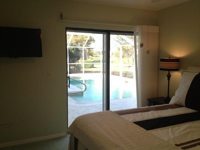 Guest bedroom, queen bed looking out over the pool