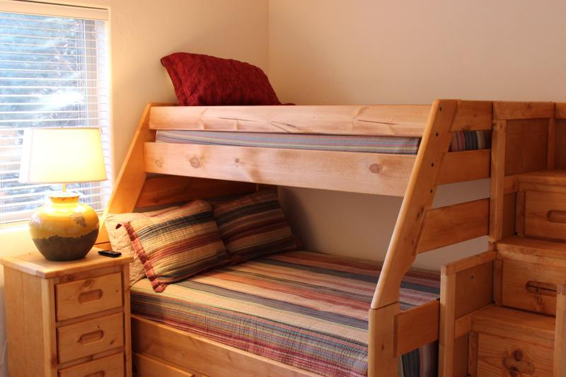 Twin/Full bunk beds with safe, sturdy stairs for storage and upper bunk access, plus flat screen TV.