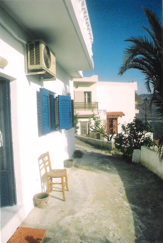 espace terrasse à l'extérieur de la maison avec les volets bleus, espace extérieur table, chaises