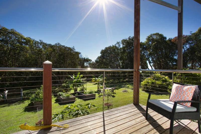 North facing (sunny) deck overlooking the vegetable garden and forest.  Track to beach at back.