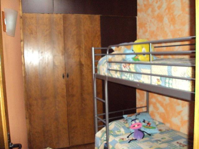 Room with bunk beds and bed below. Window on the roof to see the sky. Large wardrobe.