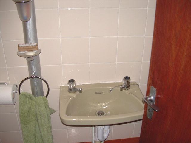 Das Waschbecken und WC, große mattierte doppelt verglaste Fenster trennen ins Bad.