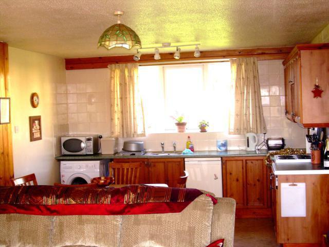 Die Küche / Esszimmer mit Blick auf Rasen und großen Bäumen und mit Licht durchflutet. Tisch und Stühle für 6 Personen.