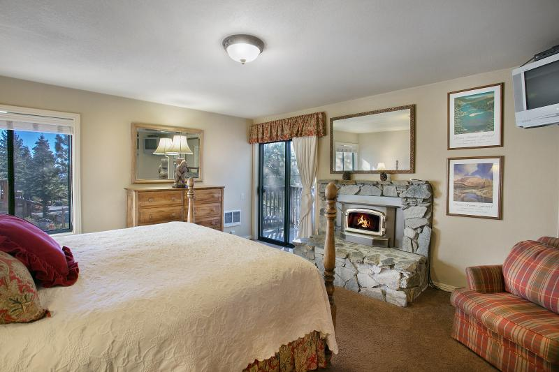 Master Bedroom With A Wood Burning Fireplace, King Bed, and A Private Balcony