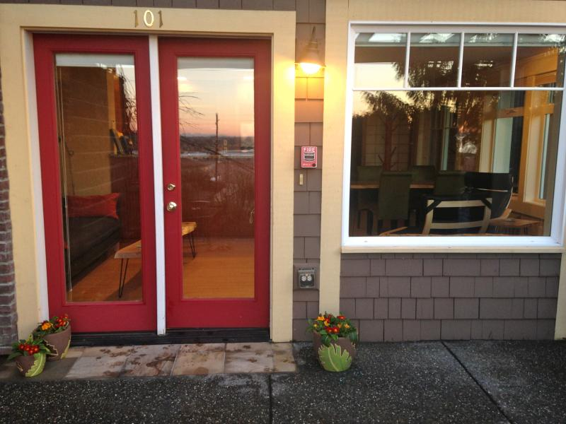 The Studio's main entrance, with sunset reflected in the glass. Summer time brings outdoor furniture