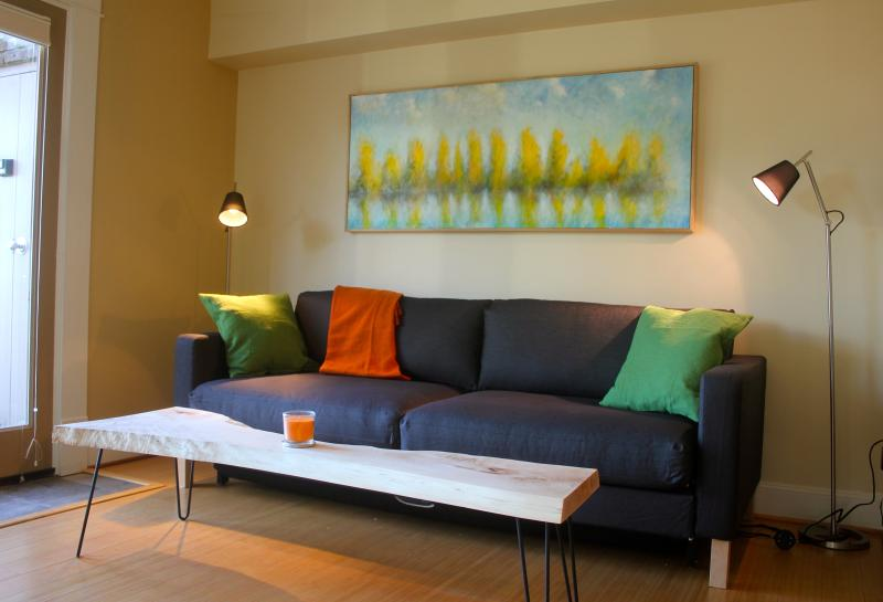 One half of the living room area, with art by local artist Tyee Callahan. The sofa becomes a double