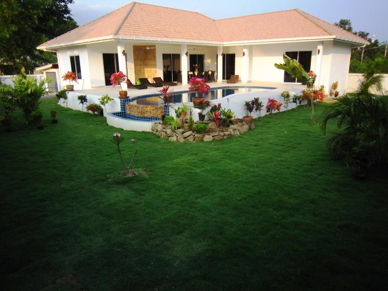 jardín con una amplia zona de césped. 2º Villa de alquiler completo, jardín con un amplio césped.