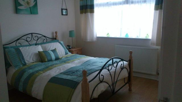 The master bedroom, blue and green lined with a stunning double bed, lovely light room with alarm.