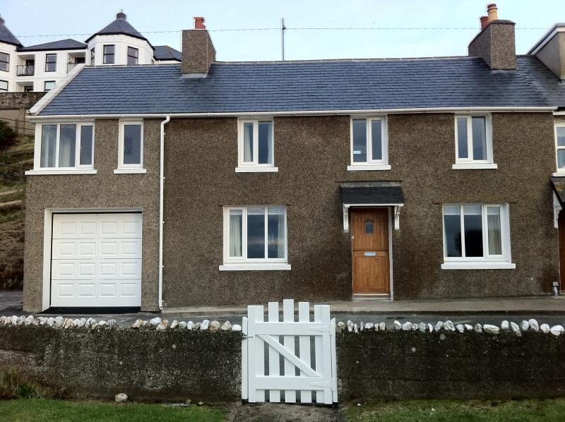 Front of cottage - showing garage and upstairs lounge with views of Bradda Head and the beach.