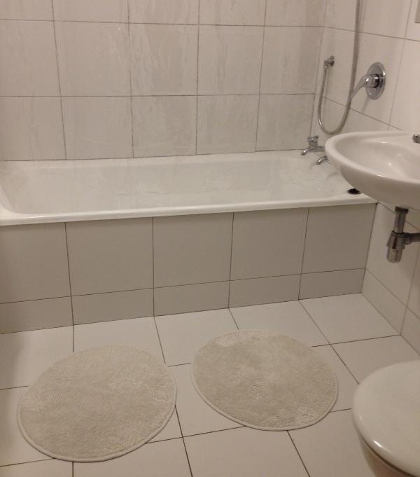 Tiled bathroom with shower over the bath.