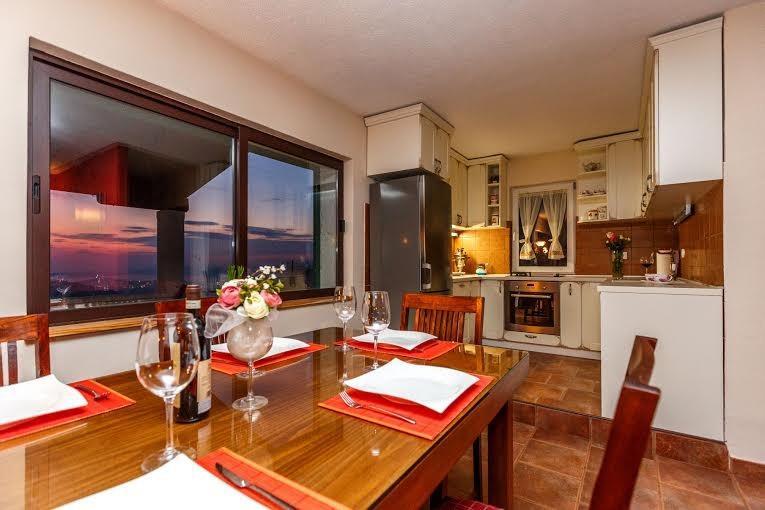 Zona pranzo e soggiorno con cucina completamente attrezzata, camino e splendida vista a Spalato