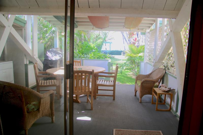 Large covered lanai with gas BBQ, large dining table, outside seating, and washer/dryer