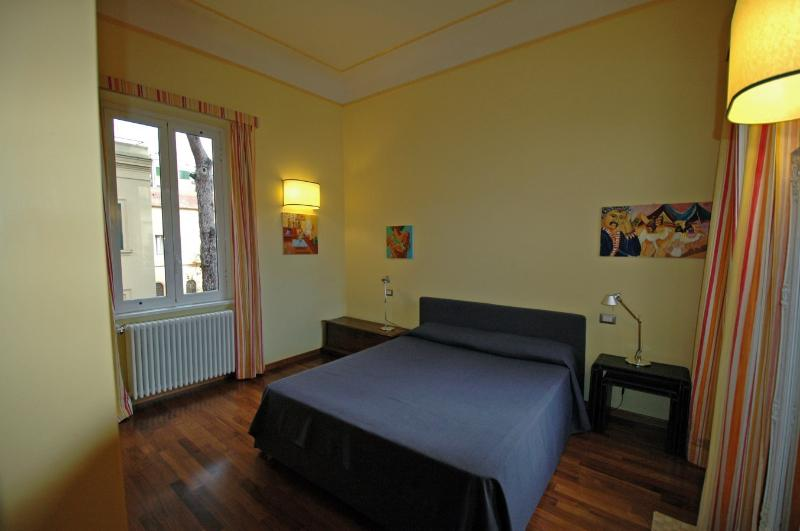 the first large room with double bed, wardrobe, desk and two windows