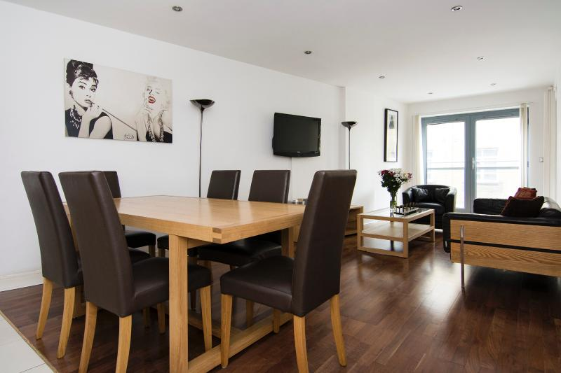 Open plan living room with solid wood floors, underfloor heating and private balcony