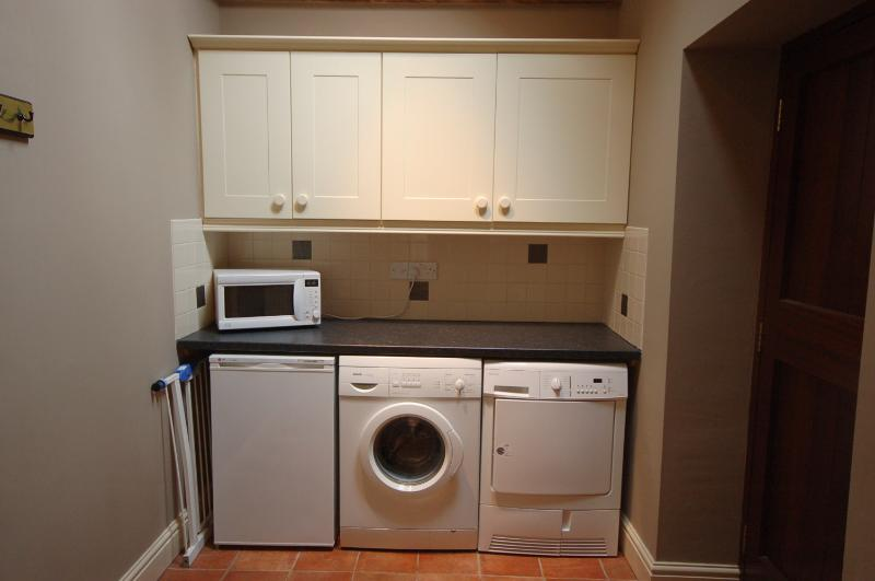 Utility with Microwave, Freezer, Washing machine and Tumble dryer.