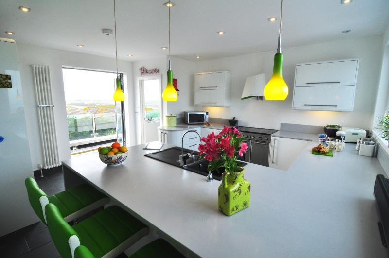 Keuken met een uitgebreid ontbijt bar, wat leidt tot een balkon met verreikende land en uitzicht op de kust.