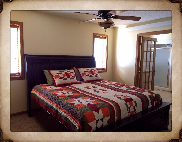 Master bedroom with a beautiful quilt and plenty of room to stretch.