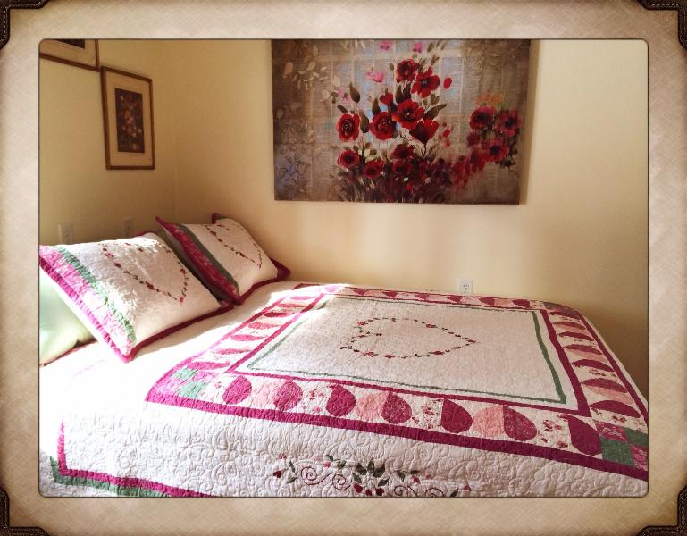 Queen room with beautiful floral accents and comfortable bed.