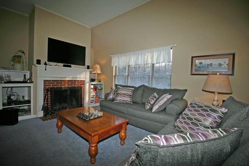 Sala de estar espaçosa com grande tela de tv e lareira