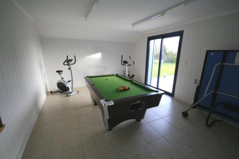 sala de juegos de comedor con mesa de billar y mesa de ping-pong.