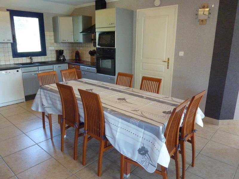 Mesa de comedor con sillas y la puerta (con llave) a la piscina cubierta deslizante.