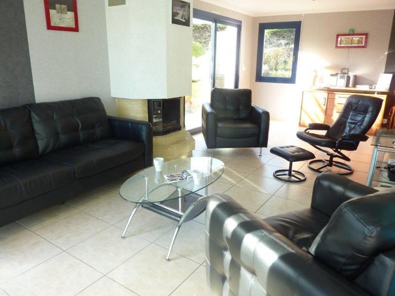 Salón con sofá de tres plazas, dos sillones y una chimenea.
