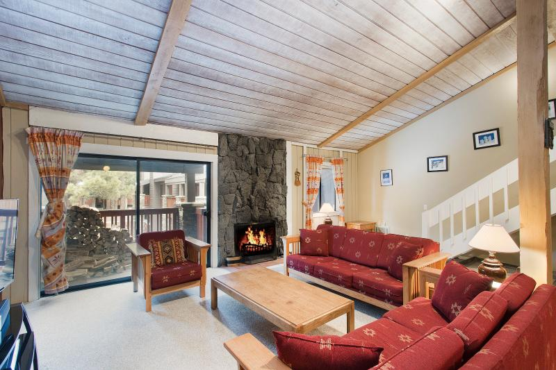 The Summit #H108 Living Area with A Wood Burning Fireplace and Vaulted Ceilings