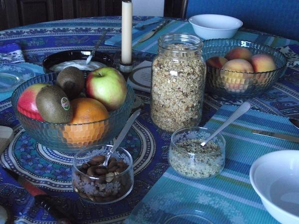 Cashew and cranberry granola with maple syrup topped with fruit and hemp seeds with banana muffins.