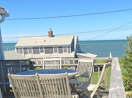 One house back and about 100 feet from the beach in Brewster with outstanding water views from the upper deck and most of the house.