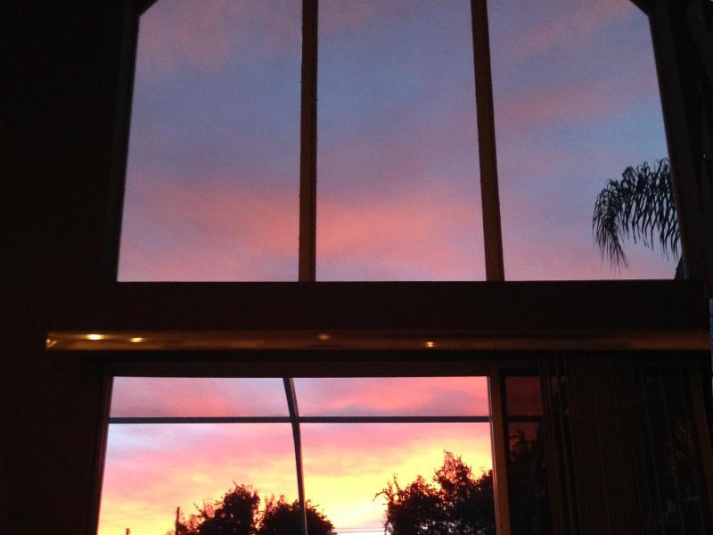 Une vue d'un beau coucher de soleil de la fenêtre surdimensionnée de la salle familiale