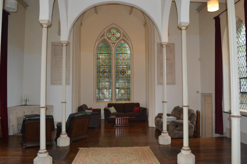 Fantastic huge living room with original stained glass window.