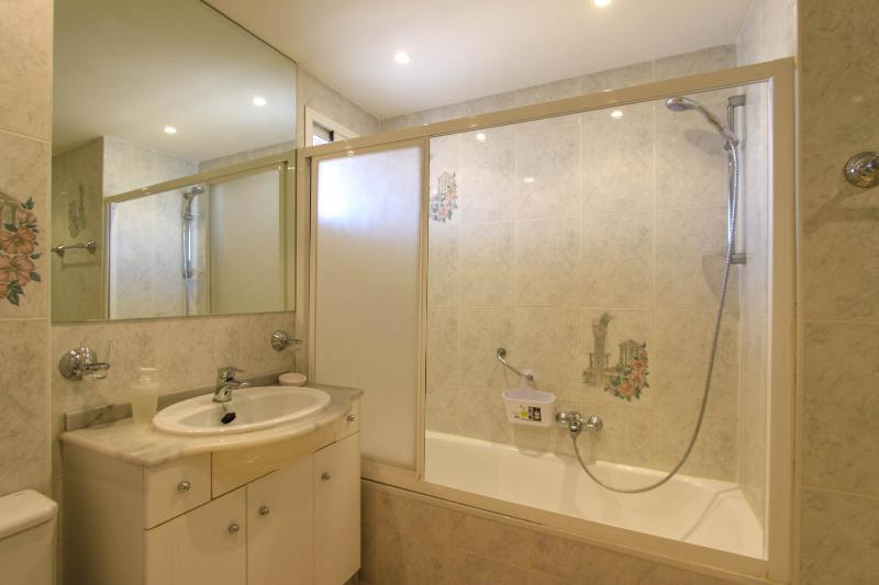Bathroom  with shower unit and small window to balcony