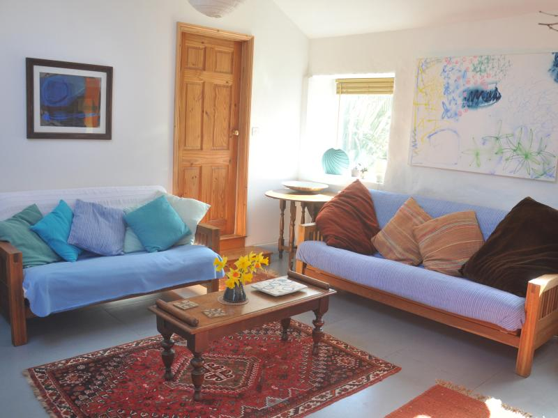 The living room is bright and sunny, it has a modern feel with dual aspect windows onto the gardens