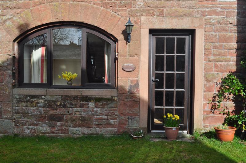 Puerta trasera de la casa que conduce a una zona de césped para los huéspedes