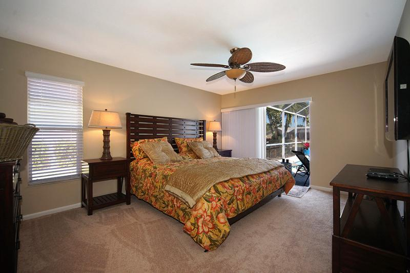 Master King Bedroom with large TV, dressing area, walk-in closet, and slider to lanai. North Wing