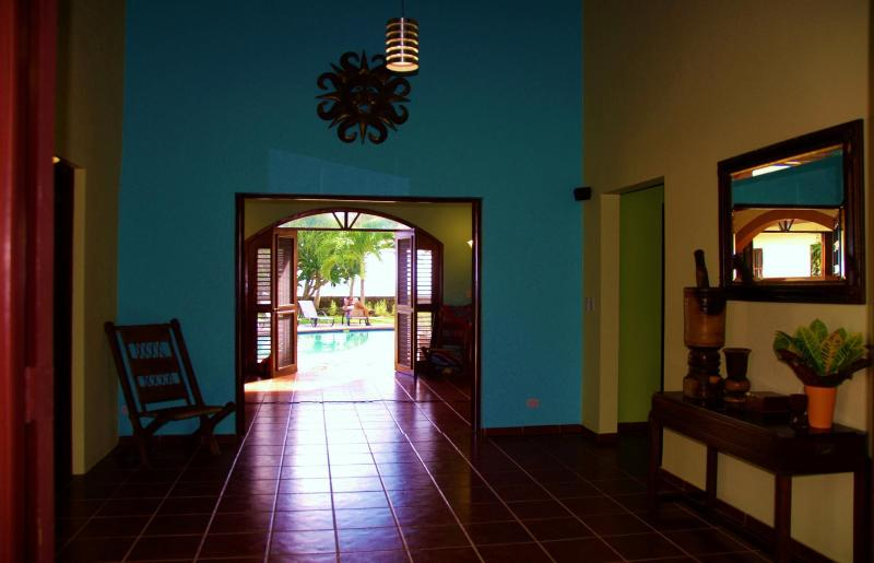 The foyer opens to the kitchen (right), bedroom 2 (left) and thru to the pool and ocean.