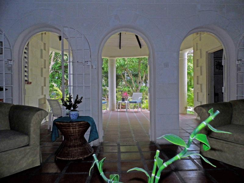 Inside your living room, looking out through the veranda to the front garden.