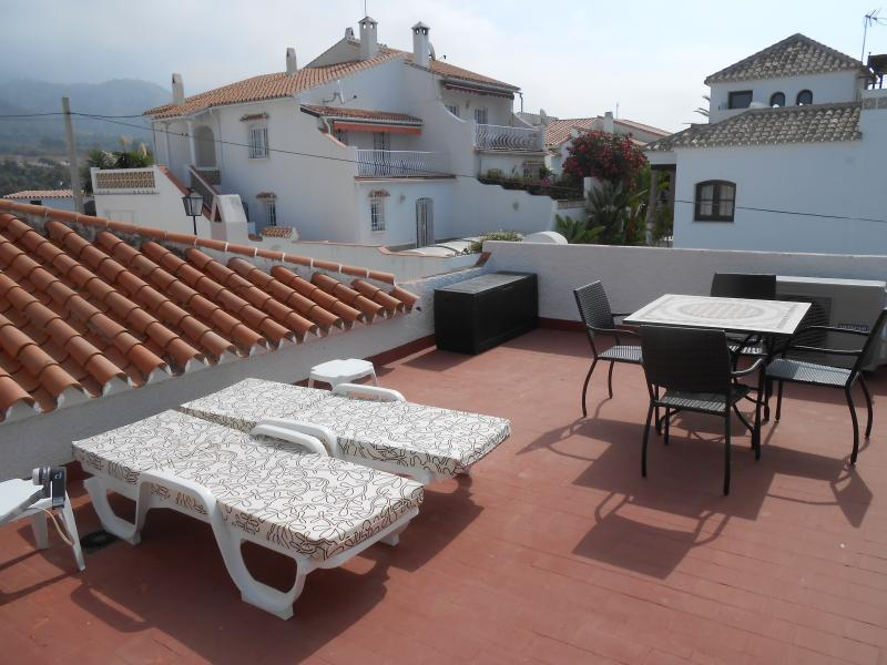 Sun loungers, dining table and armchairs on roof terrace with view over mountains and sea