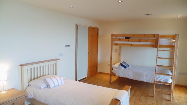 Ground floor room with two single beds and a bunk bed, all with deck access and sea views
