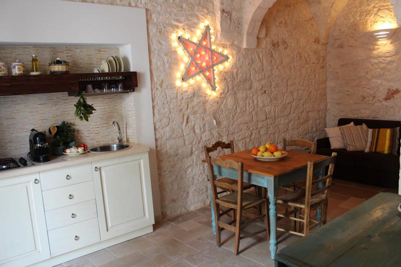 The kitchenette, the starlit on the stone wall and the old made table
