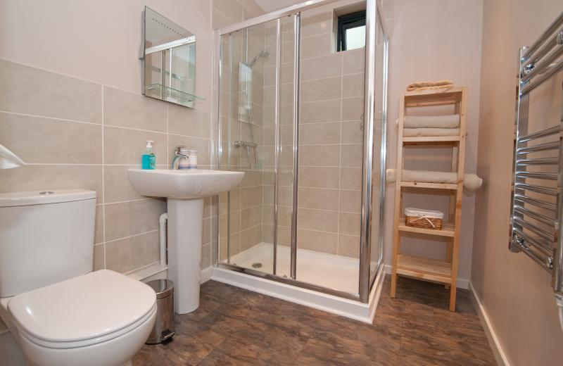 A spacious bright shower room with large shower enclosure.