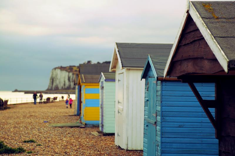 Nearby beach huts and a view of the white cliffs of Dover