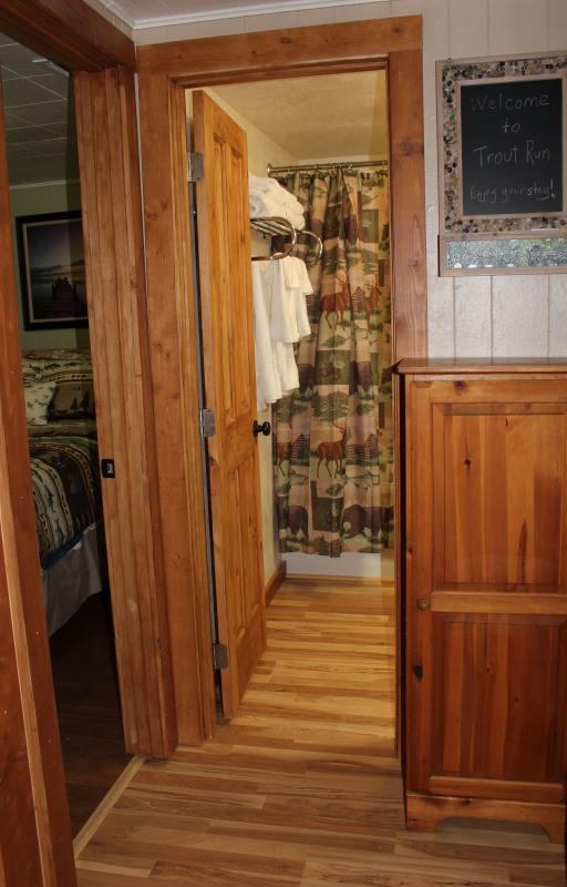 Hallway with wooden storage with extra linens