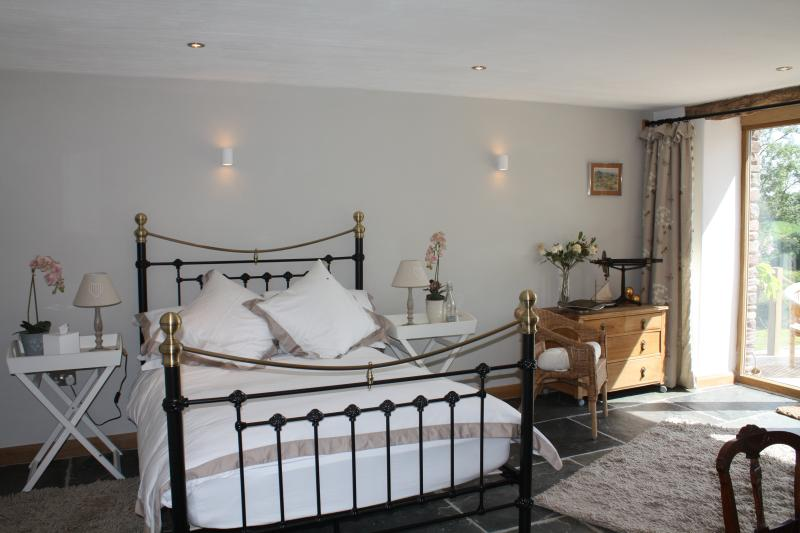 The downstairs bedroom with french windows onto the decking and views beyond...