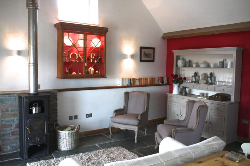 The sitting room with flagstone floors, oak beams, french windows, log burner and comfy seating