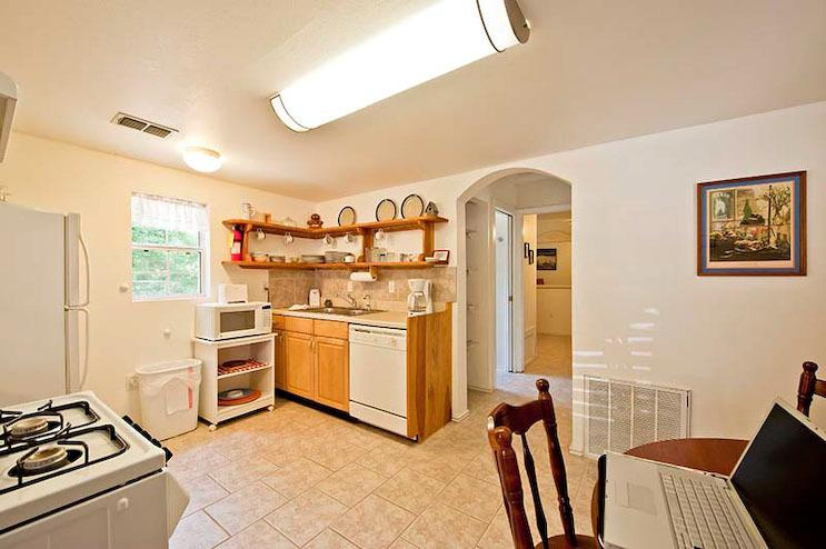 Full kitchen with stove, dishes, fridge, and dinning table.