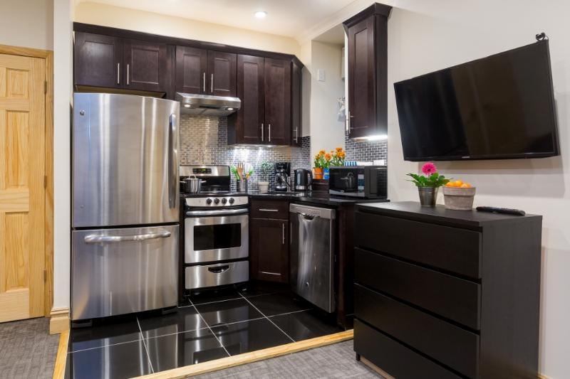 Kitchen with full-size refrigerator,  dishwasher, ceramic-topped electric stove & wood cabinets